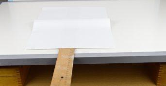 Papír udrží pravítko na stole